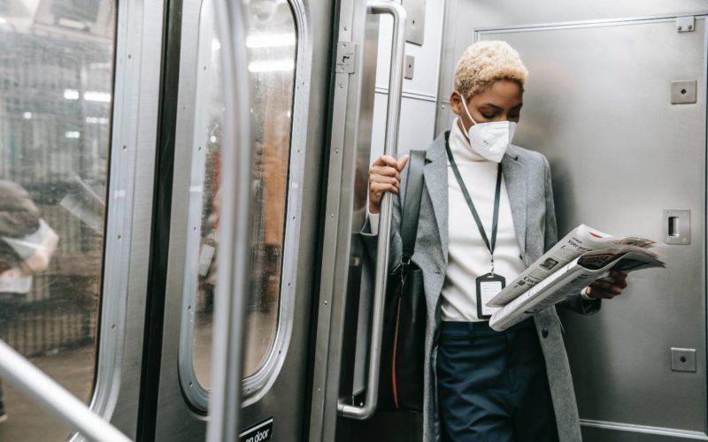 Woman riding the subway wearing a mask