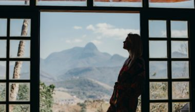Woman leaning on a windowframe with landscape background