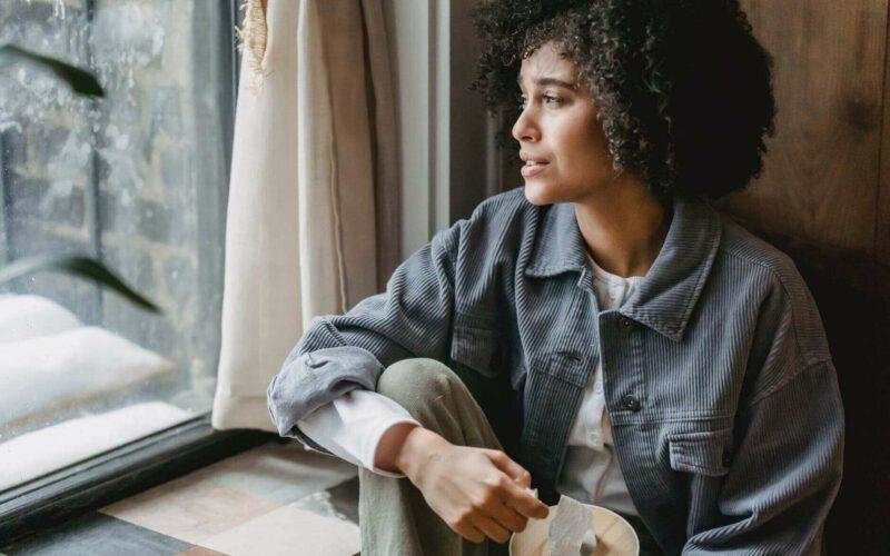 woman in blue jacket looking out window