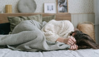 woman lying in bed covering face with blanket