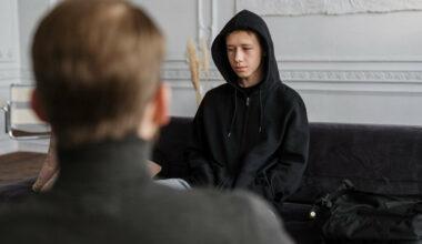 boy in black hoodie sitting across from man