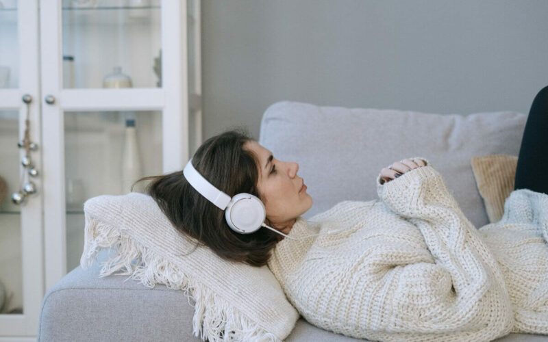 Woman lying down with headphones on