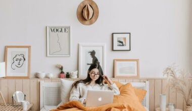woman lying in bed on computer