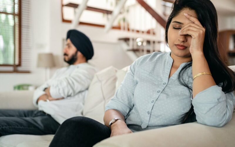 upset couple sitting apart on couch