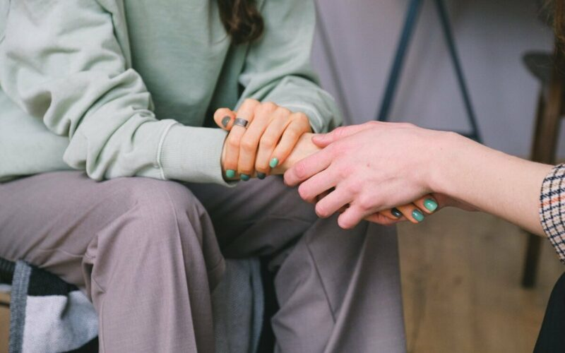 person holding woman's hands
